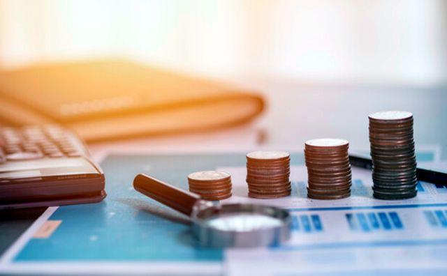 Укладка монет на финансовый отчет с лупой и калькулятором