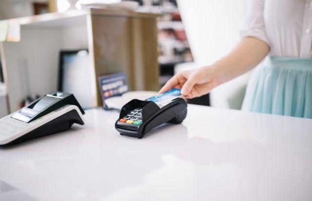 Женская рука использует кредитную карту для оплаты покупки в магазине