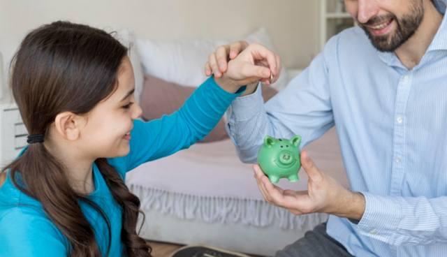 Мужчина вместе с дочерью откладывают монетку в копилку