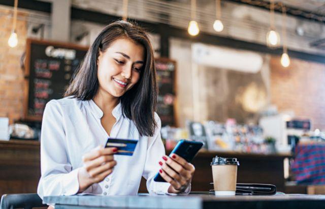 Девушка оплачивает кофе с помощью безопасного мобильного банка