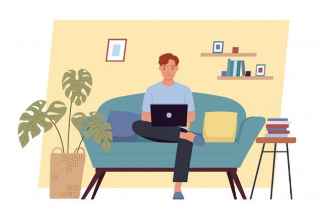 Молодой человек работает дома на диване с ноутбуком в руках