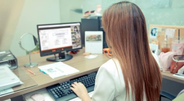 Деловая женщина с длинными волосами сидит за компьютером и совмещает работу и образование