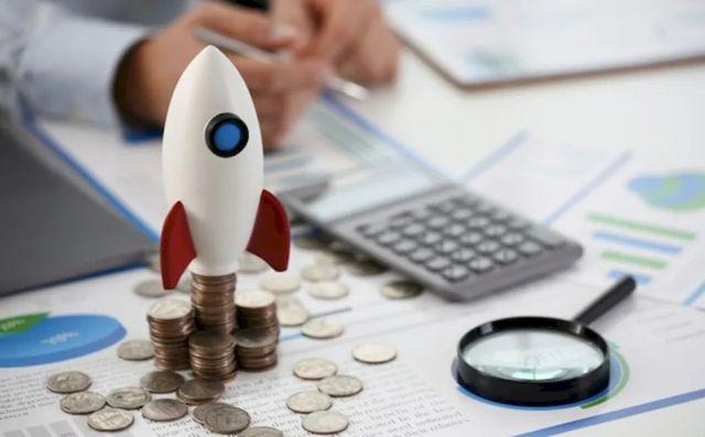 Игрушечная ракета на стопе монет как символ роста доходов