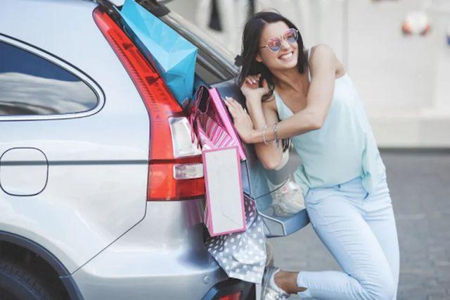Девушка пытается запихать свои покупки в багажник автомобиля