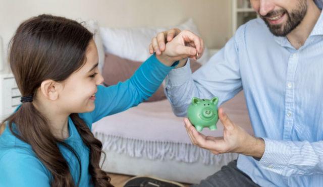 Мужчина учит дочь откладывать деньги в копилку