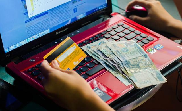 Девушка выполняет онлайн платеж с банковской карты