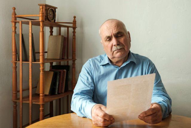 Пожилой мужчина вычитывает текст завещания