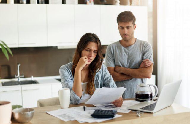 Семейная пара со страхом смотрит на долговые документы