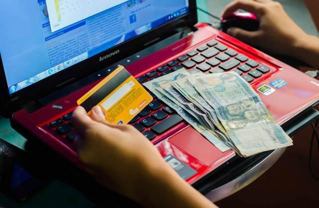 Деньги на клавиатуре ноутбука, банковская карта в руках, оплата услуг в Интернете